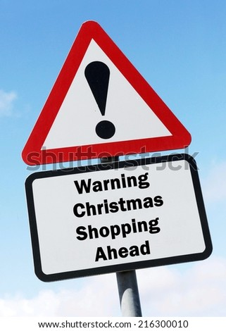 Red and white triangular warning road sign with a warning of Christmas Shopping ahead concept against a partly cloudy sky background - stock photo