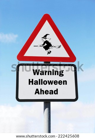 Red and white triangular warning road sign with a warning of Halloween ahead concept against a partly cloudy sky background