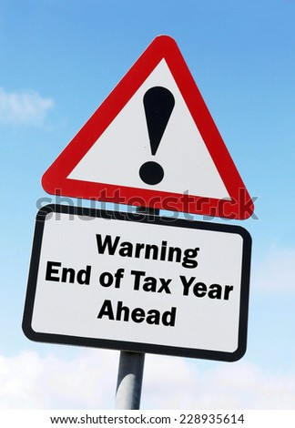 Red and white triangular warning road sign with a warning of the end of the tax year ahead concept against a partly cloudy sky background - stock photo
