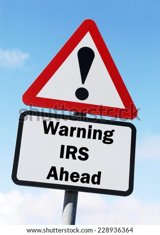 Red and white triangular warning road sign with a warning of the IRS ahead concept against a partly cloudy sky background - stock photo