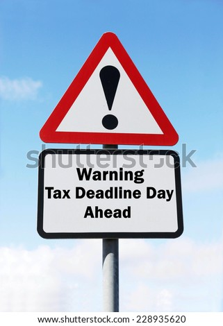 Red and white triangular warning road sign with a warning of the tax deadline day ahead concept against a partly cloudy sky background