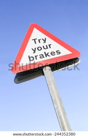 Red and white triangular warning road sign with a warning  to Try Your Brakes concept against a clear blue sky background - stock photo