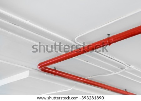 Red and white tube/pipe system under ceiling in a parking lot - stock photo