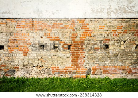 Red and white wall background and some green grass - stock photo
