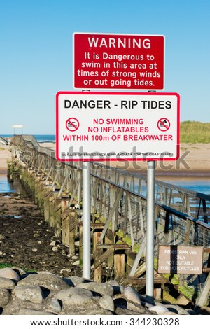 Red and white warning signs at the beach in Lossiemouth, Scotland