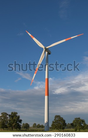 Red and white wind turbine against a blue sky
