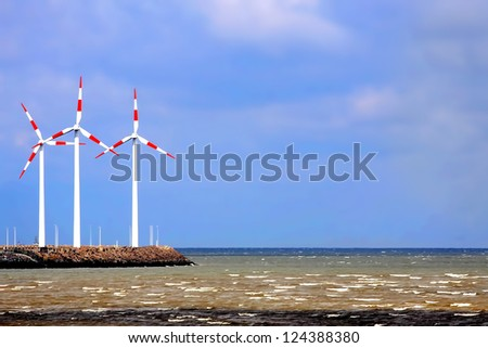 Red and white windmills towers over a landscape of sea - stock photo