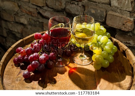 Red and white wine between bunches of grapes - stock photo