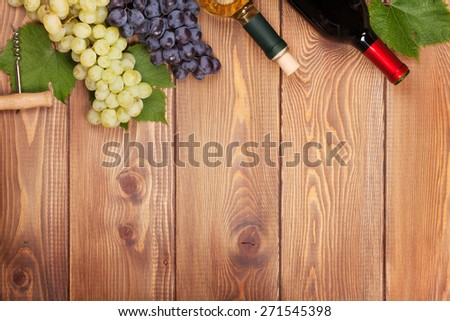 Red and white wine bottles and bunch of grapes on wooden table with copy space   - stock photo