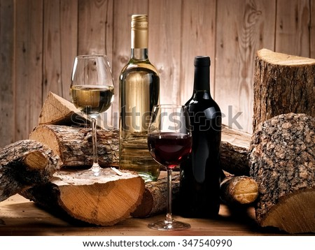Red and white wine bottles and glasses in wood - stock photo