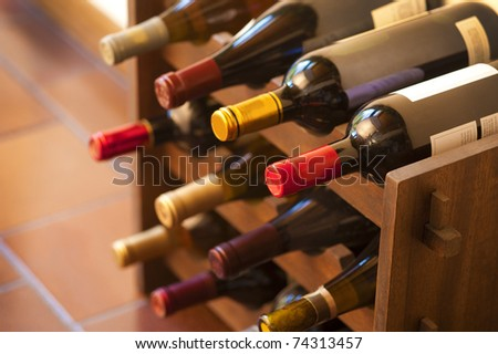 Red and white wine bottles stacked on wooden racks shot with limited depth of field - stock photo