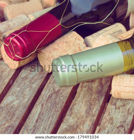 red and white wine bottles with corks on wooden table - stock photo
