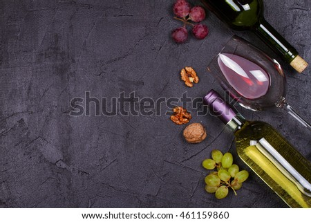 Red and white wine glass and bottle. Grape and nuts on black background. View from above, top studio shot