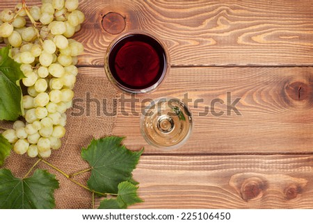 Red and white wine glasses and bunch of grapes on wooden table with copy space - stock photo