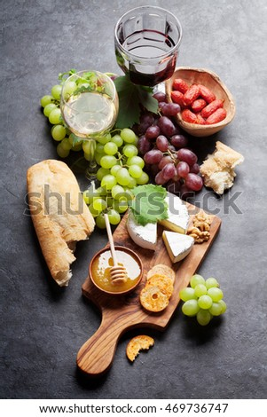 Red and white wine, grape, cheese and sausages on stone table