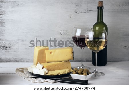 Red and white wine in glasses and bottle and assorted cheese with olives on rustic wooden background. - stock photo
