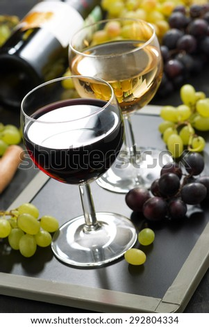 red and white wine in glasses, fresh grapes in the background, vertical, close-up - stock photo