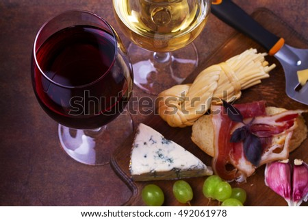 Red and white wine. Smoked cheese, grape, prosciutto, garlic and bread. Wine and food still life. View From Above, Top Studio Shot