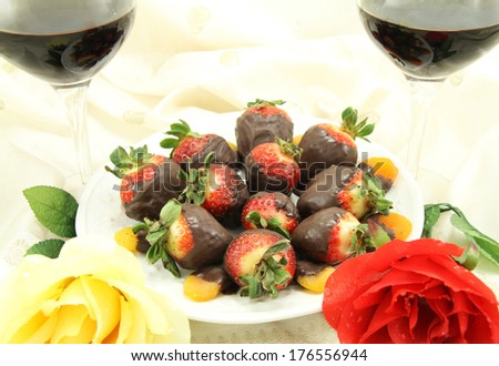 Red and white wine with chocolate covered strawberries, chocolate covered apricots and roses. - stock photo