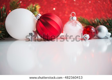 Red and white xmas ornaments on white and red glitter bokeh background. Merry christmas card. Winter holiday theme. Happy New Year. Space for text.