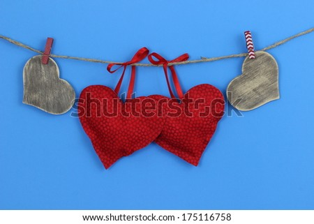 Red and wood hearts hanging on clothesline with blue background - stock photo
