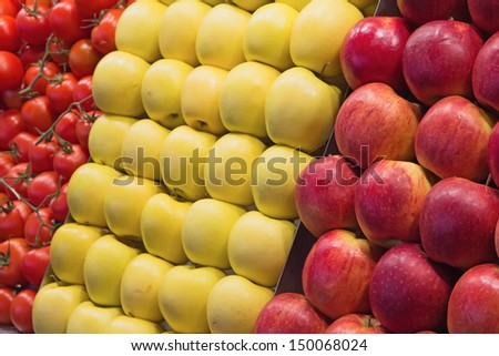 Red and yellow apples and tomatoes ready to sell on the market - stock photo