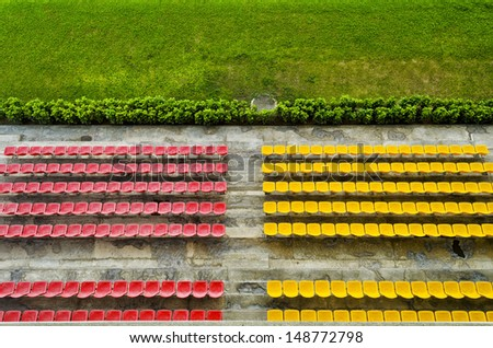 Red and yellow bleacher seats in one of the high end racetracks in the Philippines. - stock photo
