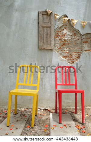 red and yellow chair on old wall