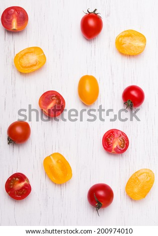 Red and yellow cherry tomatoes on the white wooden background, up view - stock photo