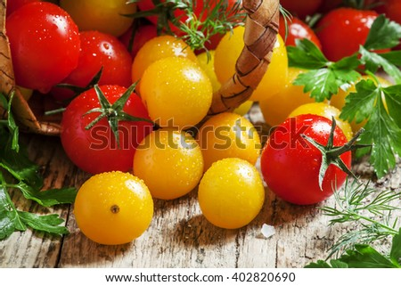 Red and yellow cherry tomatoes spill out of a wicker basket, vintage wooden background, country style, selective focus
