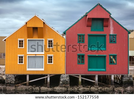Red and yellow coastal wooden houses in Norway - stock photo