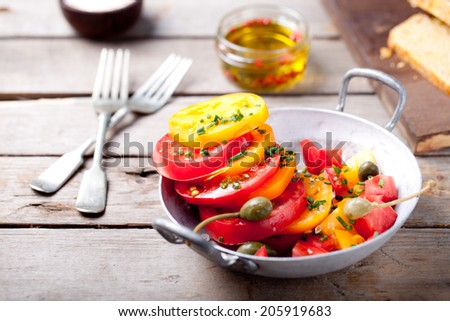 Red and yellow fresh tomato salad with capers, olive oil and carrot and oatmeal bread on a wooden background