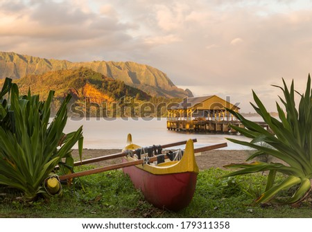 Red and yellow hawaiian canoe with outrigger on the beach at Hanalei pier at dawn as the sun lights the sky over Na Pali mountains - stock photo