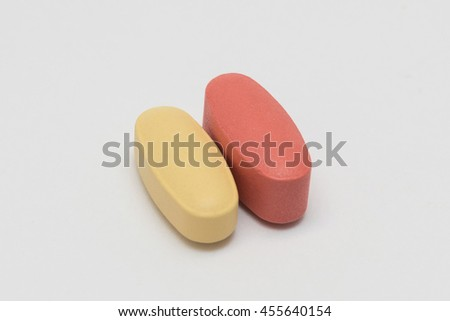 Red and yellow medicine pills heap. Isolated on white background. - stock photo