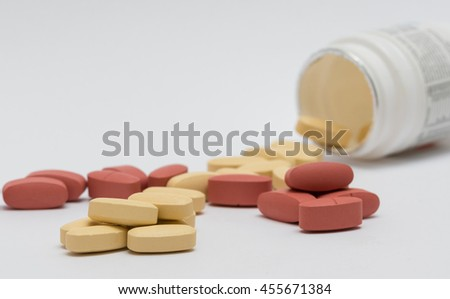 Red and yellow medicine pills spilling out of a bottle. Isolated on white background. - stock photo