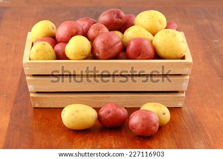 Red and yellow new potatoes in wooden box in horizontal format