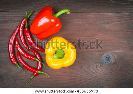 Red and yellow paprika with chilli peppers on wooden background - stock photo