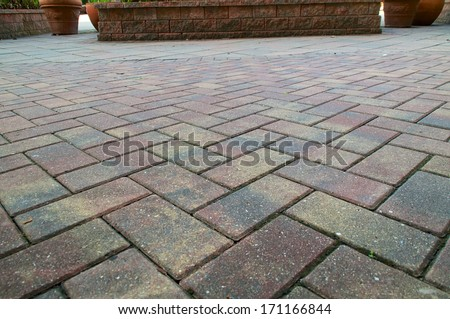 Red and Yellow pavers or bricks laid in a criss cross pattern fills the frame.  - stock photo