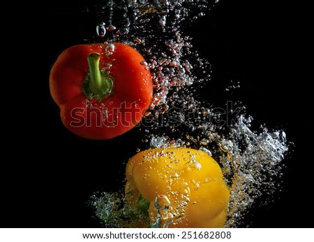 Red and yellow peppers, falling into the water with air bubbles. Photo on black background. - stock photo