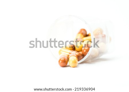 red and yellow pills out of container on white background - stock photo
