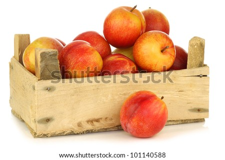 red and yellow plums in a wooden crate on a white background - stock photo