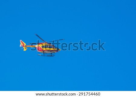 Red and yellow rescue helicopter moving in blue sky with blur propeller - stock photo