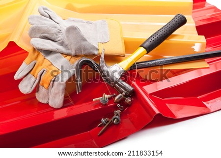 Red and yellow roof, hammer, screws, gloves, scrap, and the plummet - stock photo