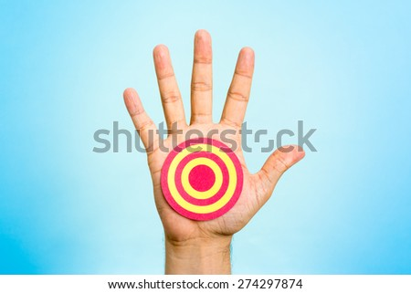 Red and yellow shooting range target on palm of hand, with blue background. Achieving goal concept. - stock photo