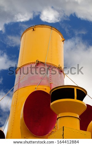Red and yellow smokestack on an old steamer ship of the Year 1912 - stock photo