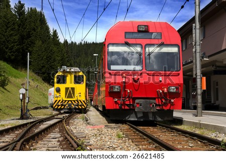 Red and yellow train at a train station in Swiss. - stock photo