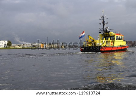 Red and yellow trawler with Nederland flag in Amsterdam harbor on a rainy day