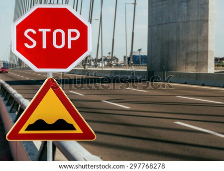 Red and yellow triangular warning road sign with STOP sign a warning of a bumpy road ahead on a rod on bridge - stock photo
