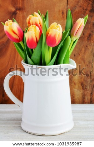 Red and yellow tulips in vintage jug in vertical format and shot in natural light