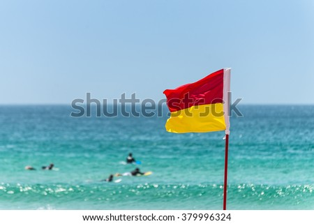 Red and yellow Warning Sign Flag marking the limit of the safe swimming area on a beach under a blue summer sky